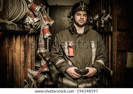 Firefighter in storage room with fire hoses  - stock photo