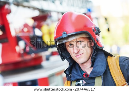 firefighter in uniform in front of fire engine machine and fireman team - stock photo