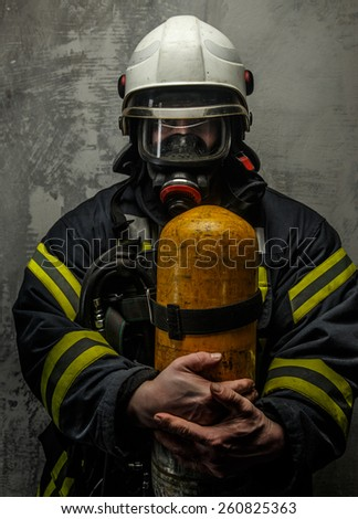 Firefighter in uniform with axe and oxygen on grey background - stock photo