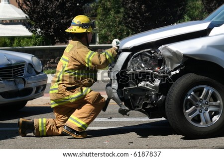 Firefighter opening the hood of a car after a car accident - stock photo