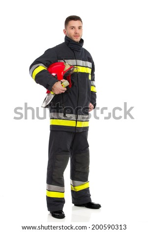 Firefighter posing and holding red helmet under his arm. Full length studio shot isolated on white. - stock photo