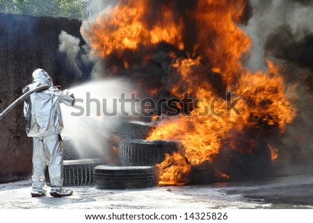 firefighter  quenches  a burning tires - stock photo