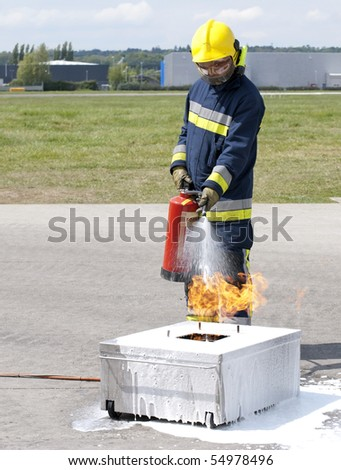 Firefighter using fire extinguisher - stock photo