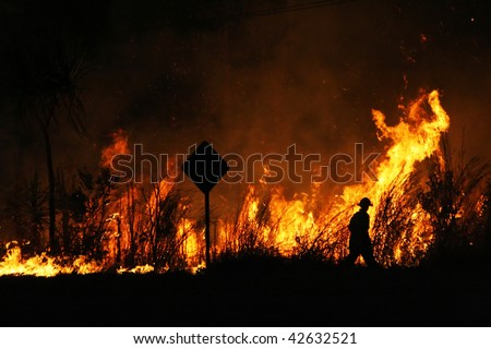 Firefighter walking around a controlled bushfire next to the road. - stock photo