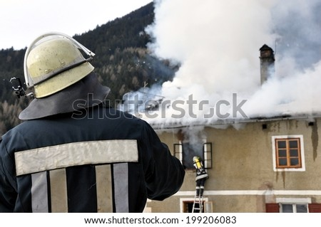 Firefighter watching a fire attack on roof house - stock photo