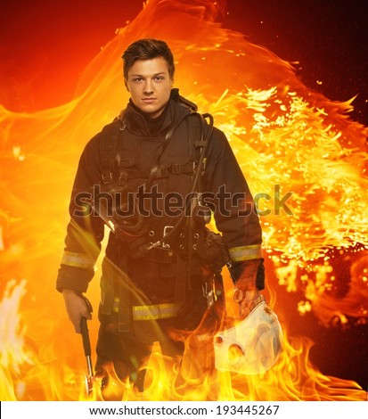 Firefighter with helmet and axe in a flame - stock photo
