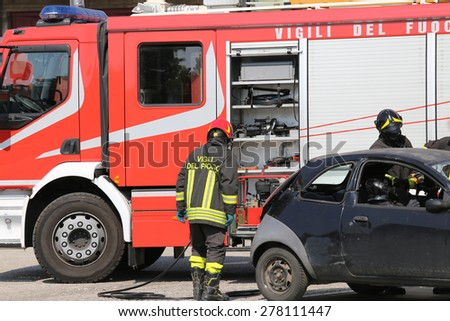 firefighters and relieve the injured in car after road accident - stock photo