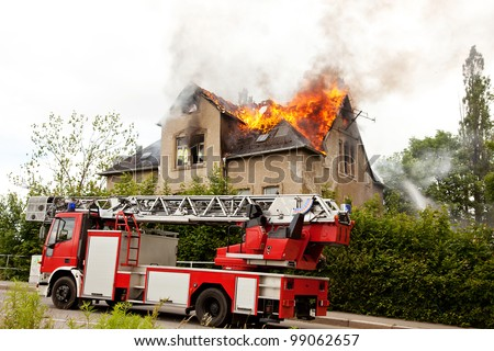 Firefighters at house fire - stock photo