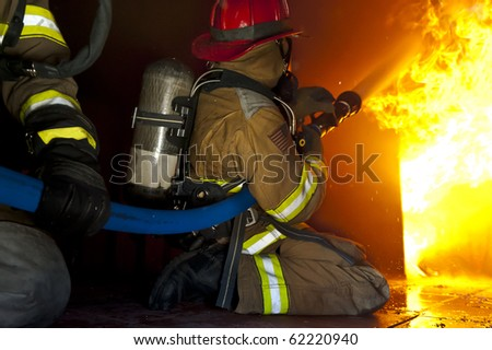 Firefighters attack a fire in a training prop. - stock photo