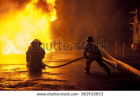 Firefighters controlling water hose - stock photo