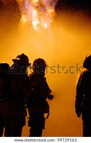 firefighters fight a blaze as a team using a water hose - stock photo