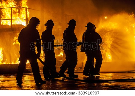 Firefighters hosing down fire - stock photo