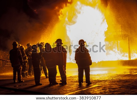 Firefighters observing structural fire - stock photo