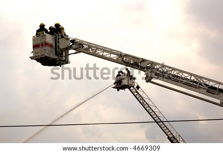 firefighters on ladder platform - stock photo