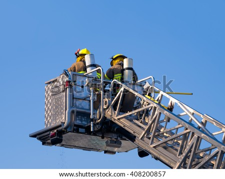 Firefighters on platform isolated on blue sky - stock photo