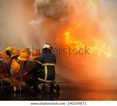 Firefighters prepare to attack a propane fire. - stock photo