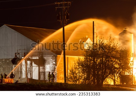 Firefighters Protecting Structures with Two Streams of Water in the Night - stock photo