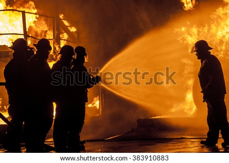 Firefighters spraying burning structure with water - stock photo