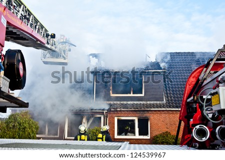 Firefighters turntable ladder at house fire - stock photo