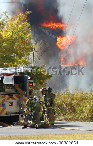 Firefighters work near a fire.  All identification marks have been removed. - stock photo