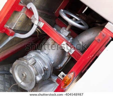 Firefighting equipment on red fire truck. Water hydrant closeup photo with selective focus - stock photo