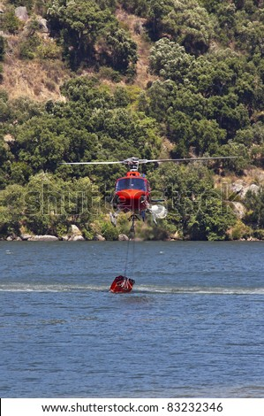 Firefighting helicopter collecting  water in the Douro river  to extinguish the forest fire - stock photo