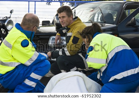 fireman and paramedic discussing the course of action,  carrying for an woman ad the side of a car crash - stock photo