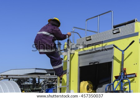 Fireman climbing down from the Fire truck .  - stock photo
