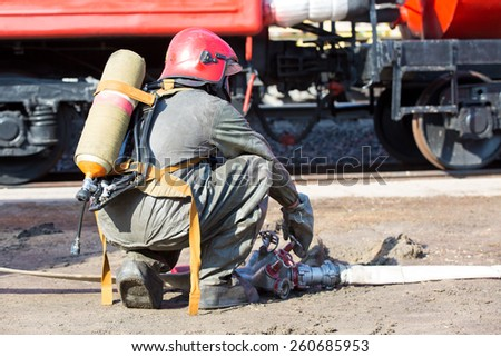 Fireman connecting firehose and controlling remote water supply pipeline during fire fighting and rescue work - stock photo