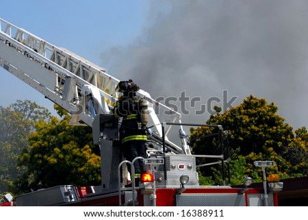 Fireman Controlling Fire Engine Ladder - stock photo