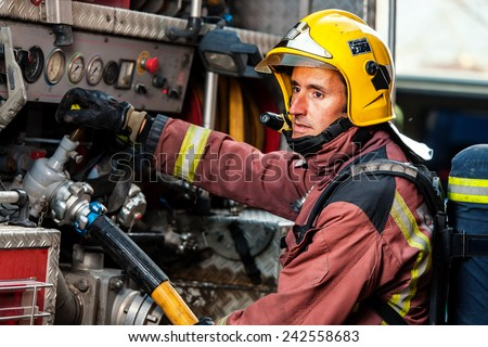Fireman controlling water pressure at back of fire truck. - stock photo