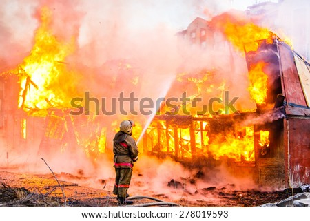 Fireman extinguishes a fire - stock photo
