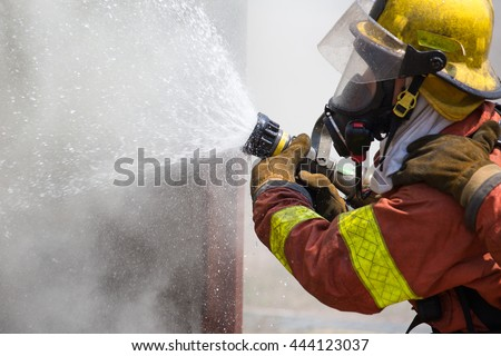 fireman in fire fighting suit spraying water to fire surround with smoke and drizzle - stock photo