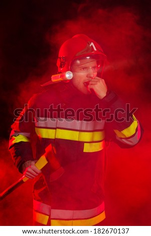 Fireman in smoke is using a walkie-talkie and looking away. - stock photo