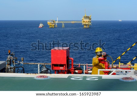fireman is guarding for offshore helicopter before start up engine at oil rig platform - stock photo