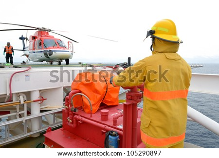 fireman is guarding for offshore helicopter before start up engine at oil rig platform in the gulf of thailand. - stock photo
