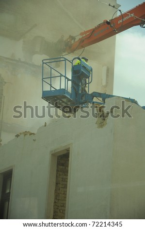 fireman on ladder trying to save old building - stock photo