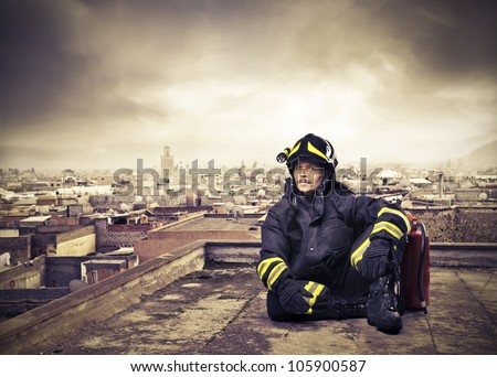 Fireman sitting on the rooftop of a skyscraper over a big city - stock photo