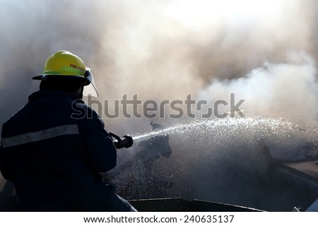 Fireman spraying water on a burnt out and smoking vehicle - stock photo