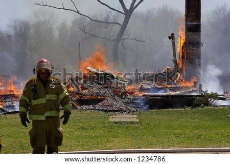Fireman with burned house - stock photo