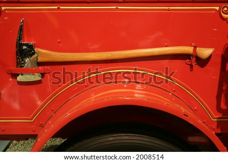 firemans' axe on side of vintage fire engine - stock photo