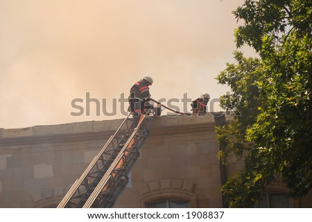 Firemen at the roof during fire - stock photo