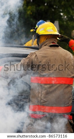 Firemen at the scene of a serious car accident on a dark, rainy fall day.  Part of a series. - stock photo