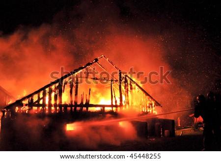Firemen direct water stream on burning house - stock photo