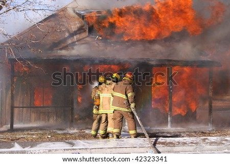Firemen fighting a house fire. - stock photo