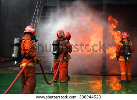 Firemen fighting the fire - stock photo