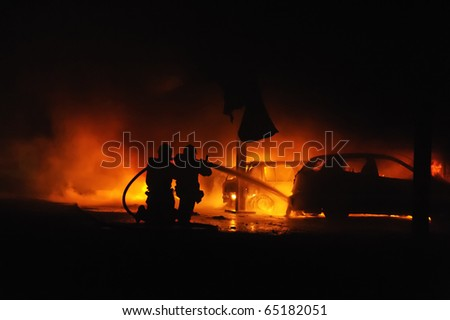 Firemen fighting vehicle fire at night - stock photo
