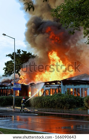 Firemen in action on burning ruins of building - stock photo