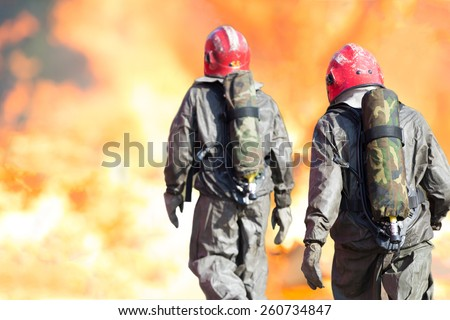 Firemen with full structural firefighting kit during rescue operations for fighting a raging fire with huge flames - stock photo