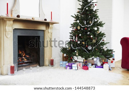 Fireplace and Christmas tree with presents in living room - stock photo